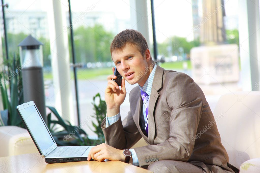 Businessman sitting at table in office hall, talking on mobile phone and using laptop computer  — Photo #4235528