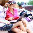 Closeup of happy young friends using laptop — Foto Stock