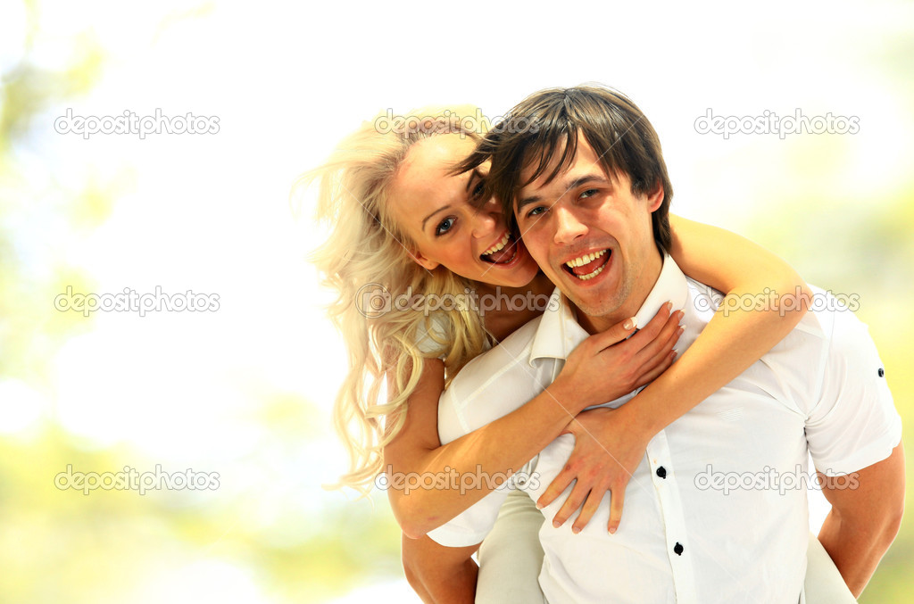 Happy young female enjoying a piggyback ride on boyfriends back against white  — Stock Photo #4248523