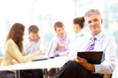 Portrait of a senior business man attending a conference with the rest of h — Stock Photo
