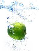 žlutá kachna hračka蓝色的水在苹果后形成泡沫的背景下被丢弃 — 图库照片