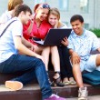 Stock Photo: Group of five students outside sitting on steps