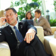 Stock Photo: Business man speaking on the cell phone while in a meeting