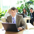Young executive working on a laptop with colleagues in the background — Stock Photo