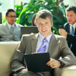 Portrait of a happy young business man with colleagues in the background — Stock Photo