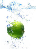 A background of bubbles forming in blue water after apple are dropped — Stock Photo
