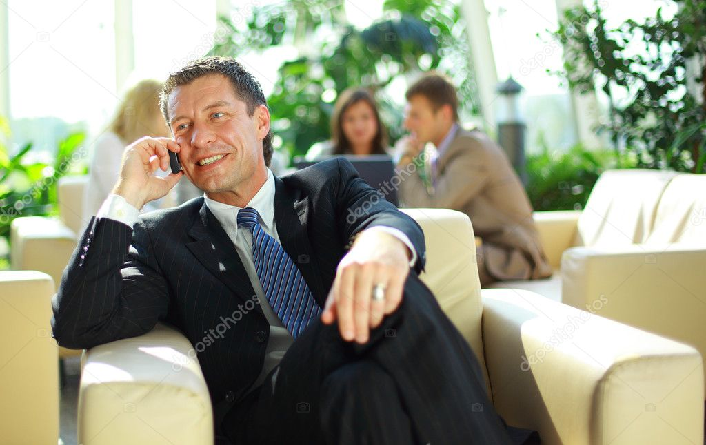 Business man speaking on the cell phone while in a meeting  — Stock Photo #4279628