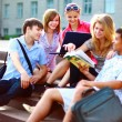 Group of five students outside sitting on steps - Foto Stock