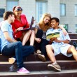 Group of five students outside sitting on steps - Stockfoto