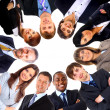 Group of business standing in huddle, smiling, low angle view — Stock Photo #4297015