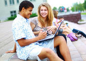 Closeup of happy young friends using laptop — Stockfoto