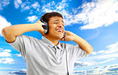 Young happy man listening to music and singing — Stockfoto