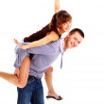Happy young female enjoying a piggyback ride on boyfriends back against whi — Stock Photo