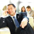 Concentrating businessman on call, coworkers talkling in background — Stock fotografie