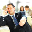 Concentrating businessman on call, coworkers talkling in background — Stock Photo
