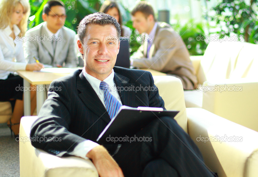 Happy business man with colleagues at a conference in the background  — Stock Photo #4335934