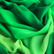 Background of emerald green fabric making curves — Stock Photo