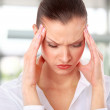 Young woman suffering a headache over white background — Stock Photo