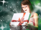 Beautifull girl opening x-mass magic present. Christmas — Stock Photo