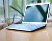 Modern laptop isolated on white with reflections on glass table. — Stock Photo