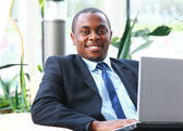 Portrait of a handsome young business man with a laptop — Stock Photo