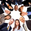 Group of business standing in huddle, smiling, low angle view - Stock Photo