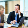 Foto de Stock  : Business man speaking on the phone while in a meeting