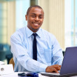 Stock Photo: Portrait of a happy African American entrepreneur displaying computer lapto
