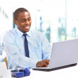 Portrait of a happy African American entrepreneur displaying computer lapto — Stock Photo