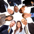 Group of business standing in huddle, smiling, low angle view — Stock Photo #4668451