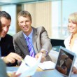 Stock Photo: Successful business team with document on table with laptop
