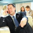 Business man speaking on the cell phone while in a meeting — Stock Photo #4673191