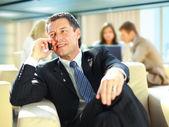 Affärsman som talar på mobilen medan i ett möte — Stockfoto