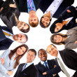Royalty-Free Stock Photo: Group of business standing in huddle, smiling, low angle view