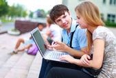 Closeup of happy young friends using laptop — Stock Photo