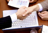 Handshake over paper and pen,blurry computer in the background — Stock Photo
