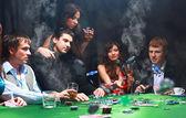 Joven lanzando fichas en la mesa mientras jugando a las cartas — Foto de Stock
