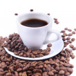 Cup with coffee and beams. Focus on coffee beans - Stock Photo