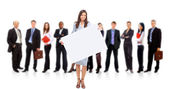 Businesswoman standing and holding a white empty billboard — Stock Photo