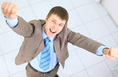 Happy businessman standing outside with arms outstretched — Stock Photo