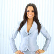 Young happy smiling businesswoman at office — Stock Photo