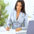 Young happy smiling businesswoman working at office - Foto Stock