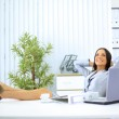 Portrait of pretty young business woman resting at her desk — Stock Photo