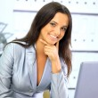 Portrait of a cute smiling businesswoman working on a laptop - Stok fotoğraf