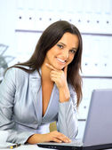 Portrait of a cute smiling businesswoman working on a laptop — Stock Photo