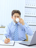 Portrait of a young business executive drinking coffee while looking at the — Stock Photo