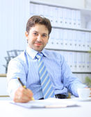Office life - friendly businessman writing — Stock Photo