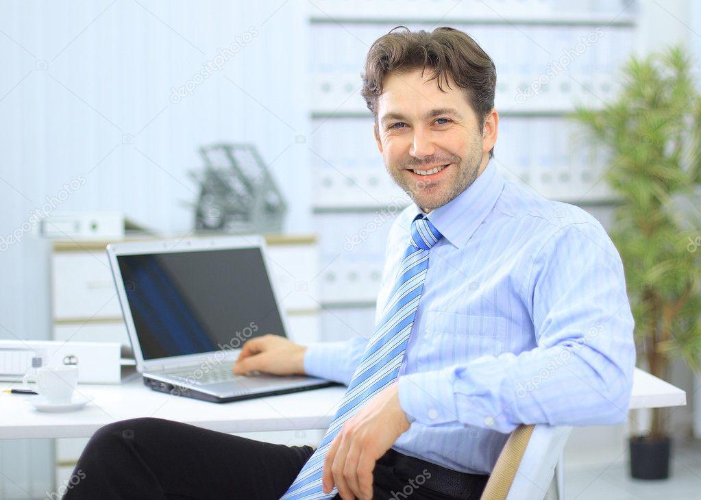 empresário sentado na mesa de escritório, a trabalhar no computador
