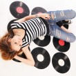 Girl lie on retro disks — Stock Photo