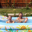 Young pair bathes in inflatable pool - Stok fotoğraf